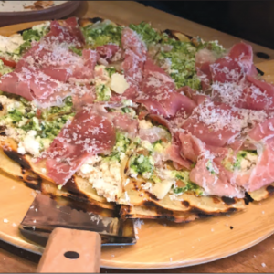 "The Frenchy ""pizza"" is made with a crêpe crust, ricotta cheese, garlicky pesto, marinated tomato confit, crispy prosciutto and French cheese shavings. (photo by Jill Weinlein)"
