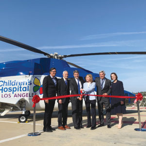 Children's Hospital Los Angeles unveiled its new Sikorsky helicopter on May 1. Taking part in the ribbon cutting in front of the CHLA-branded aircraft were Jeffrey Worthe, chair of the hospital's board of directors; Arnold J. Kleiner, a trustee on the hospital's board; Paul Viviano, the hospital's president and CEO; Kathryn Purwin, Helinet CEO and board trustee for the CHLA Foundation; Kevin Brogan, chair of the foundation's board; and Alexandra Carter, CHLA's senior vice president and chief development officer. (photo courtesy of Children's Hospital Los Angeles)