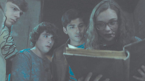 """Auggie (Gabriel Rush), Chuck (Austin Zajur), Ramón (Michael Garza) and Stella (Zoe Margaret Colletti) find a book they probably shouldn't read in """"Scary Stories to Tell in the Dark."""" (photo courtesy of CBS Films)"""