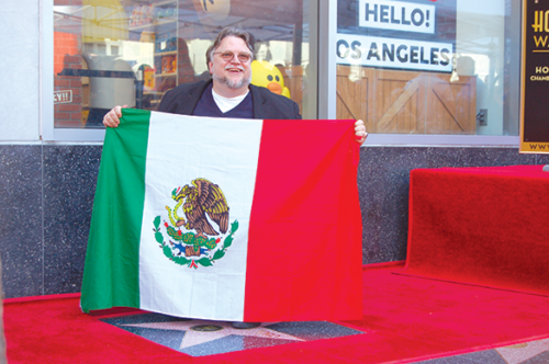 After a Mexican flag was tossed to director Guillermo del Toro by a fan, he kissed it before unfolding it over his star on the Hollywood Walk of Fame. (photo by Ryan Mancini)