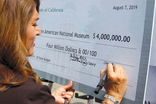 Assemblywoman Sharon Quirk-Silva (D-Fullerton) signs a state-sponsored check that will add to the $15 million used in building the Korean American National Museum in Los Angeles. (photo by Ryan Mancini)