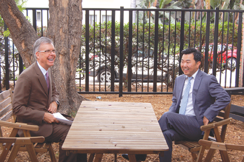 Councilman David Ryu (right) and Los Angeles City Engineer Gary Lee Moore relaxed in the courtyard during a tour of the new bridge housing center on Gardner Street. The facility was created in a building that formerly housed a library. (photo by Edwin Folven)