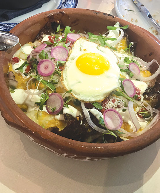 The fried egg on top of chilaquiles combines the creamy yolk with fresh vegetables and crunch tortilla chips. (photo by Jill Weinlein)