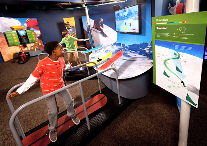 "Two children race downhill on snowboards at the ""MathAlive!"" exhibition at the California Science Center. (photo courtesy of MathAlive!)"