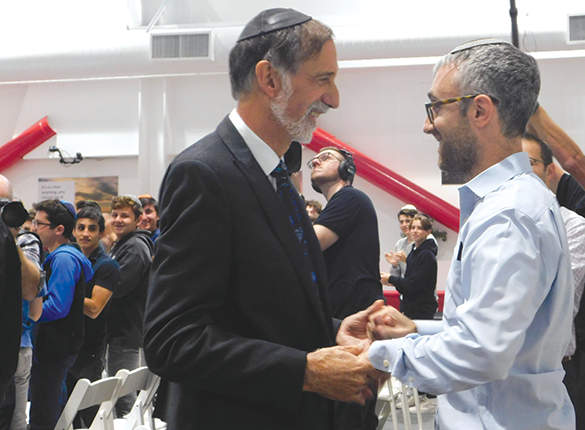 Rabbi Abraham Lieberman and Rabbi David Stein embrace after Lieberman received a Jewish Educator Award at Shalhevet High School. (photo by Kate Dietel)