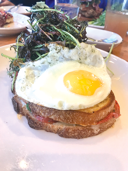 Messhall's Cali croque madame nestles avocado and oven-baked tomatoes between thick slices of crusty bread and tops it with a sunny-side-up egg. (photo by Jill Weinlein)