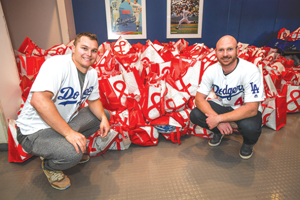 Los Angeles Dodgers players Joc Pederson (left) and Kyle Garlick helped distribute turkey dinners to families as part of the team's annual holiday giveaway. (photo by Jon SooHoo/LA Dodgers)