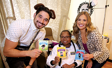 "Hannah Brown (right), who formerly starred in ABC's ""The Bachelorette"" and competed on ""The Bachelor,"" stopped by Children's Hospital Los Angeles with her ""Dancing with the Stars"" partner, Alan Bernstein (left). The pair visited Precious (center) and several other CHLA patients, distributing Halloween greeting cards and goodie bags.  (photo courtesy of Children's Hospital Los Angeles)"