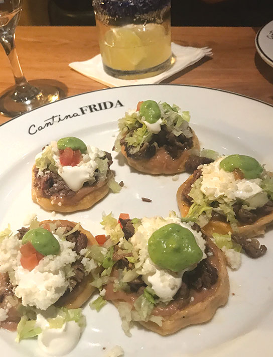 The corn-cake sopes are layered with tender pork, sour cream, chopped avocado and tomatoes. Crumbled white cotija cheese tops off this dish. (photo by Jill Weinlein)